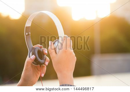 Headphones in a nice hands at sunset . Beautiful light .Good music and emotions from listening
