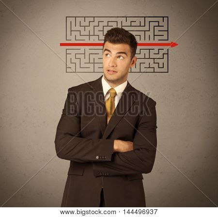 A young handsome business person making facial expression and solving maze with red arrow in front of clear, empty concrete wall background concept