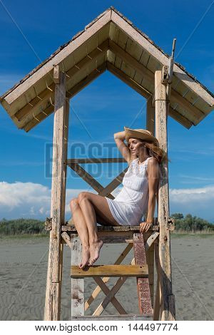young attractive girl posing on a lifeguard tower on the beach