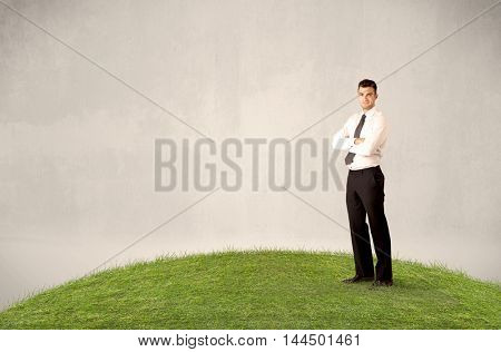 A successful caucasian elegant business man standing in small green grass with briefcase in front of clear empty background concept.
