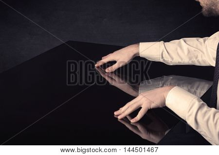 Close up of a hand touching smart table with copy space on black background