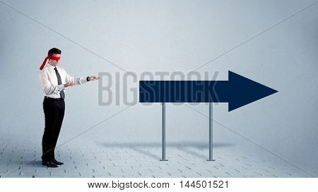 A lost young sales person with blindfolds trying to find the right path concept with large blue arrow sign pointing forward.