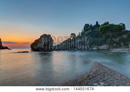 Sunrise at the coast of Taormina in Sicily with the beautiful Isola Bella