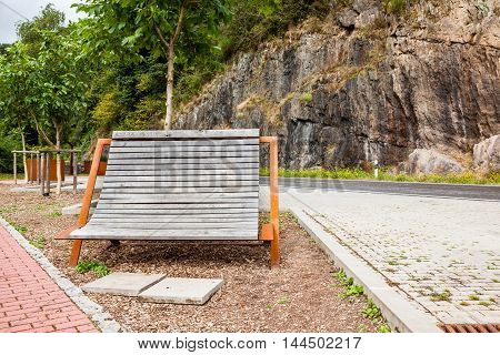 along the road in Luxembourg there is a wooden bench with iron structure