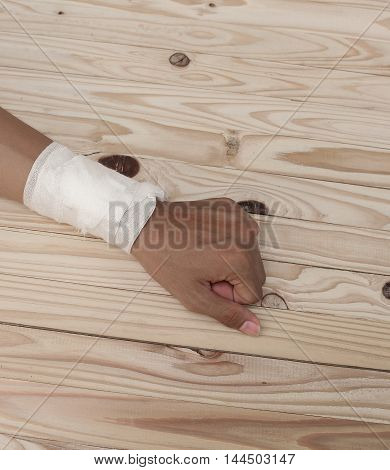 Gauze bandage the hand contusion. treating patients with hand with a wrist left male  is wrapping his injury On a wooden table