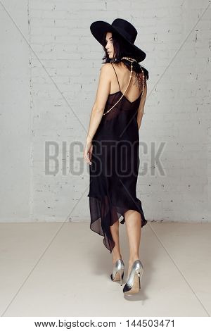 Girl in black hat staying turning away from photographer turned in profile in studio with brick walls