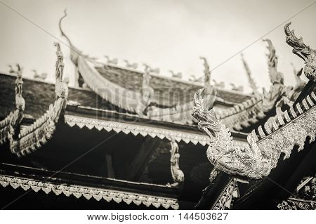 Thailand art and architecture: Naga wood carved on roof at Thai temple. Sepia tone.