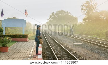 In a foggy sunshine day an asian women travelers waiting for a train on the platform at local Train Station. Copy space.