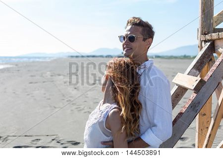 happy couple in love walking on the beach in summer white dress