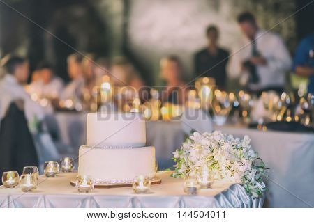 The simple white cake decorated with the silver soil candle light at party background.