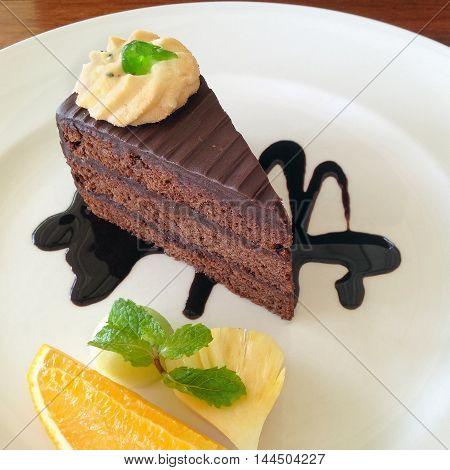 Dark chocolate cake on white dish with decorated.