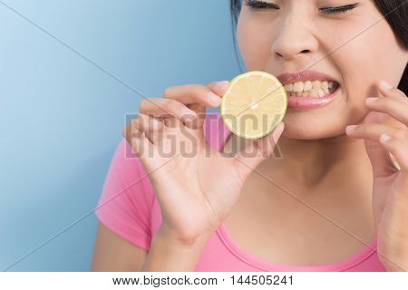 Asian young woman with hypersensitive teeth eating lemon, closeup portrait
