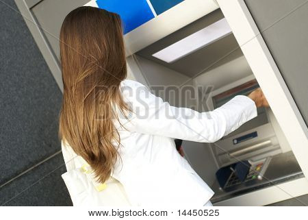 Young attractive businesswoman taking off money from the outdoor bank terminal