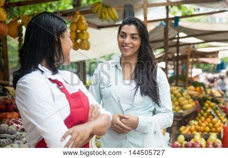 Mexican saleswoman on a farmers market talking with client
