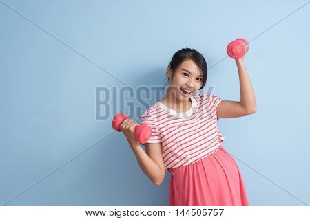 asian young pregnant sport by using dumbbell