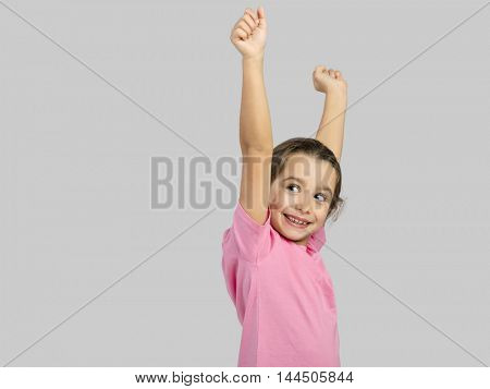 Studio portrait of a happy little girl with arms raised on air