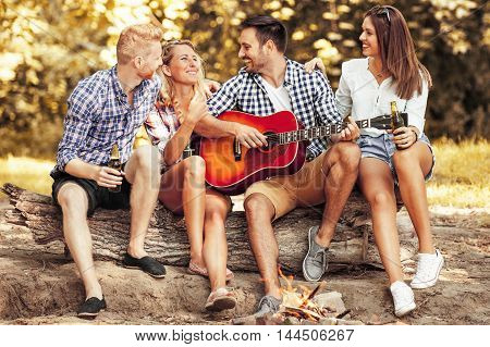 Fiends enjoying camping and playing guitar. Time to relax.