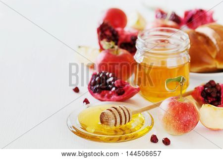 Holiday Rosh Hashana Jewish New Year traditional food.  Honey, apple, pomegranate and hala