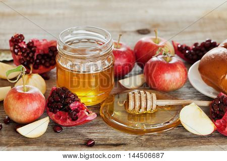 Table set with traditional food for Jewish New Year Holiday Rosh Hashana. Honey, apple, pomegranate and hala