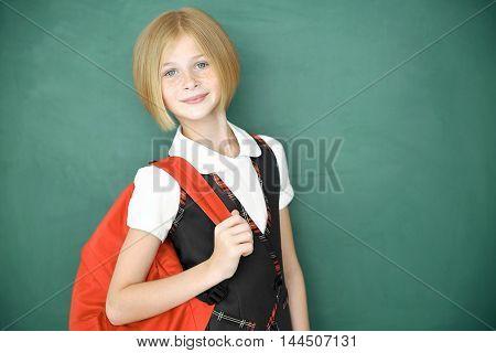 Cute schoolgirl on chalkboard background