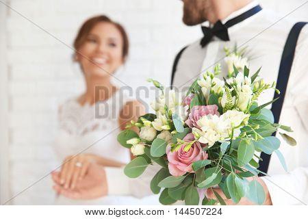 Beautiful wedding bouquet and newlyweds on background