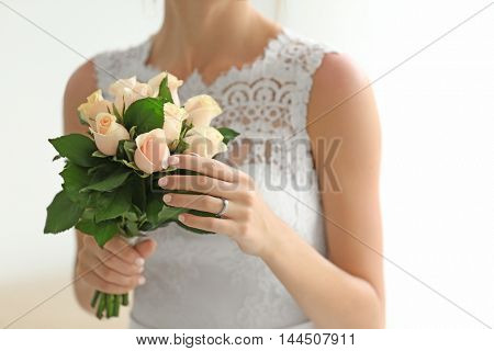 Bride in beautiful dress holding wedding bouquet
