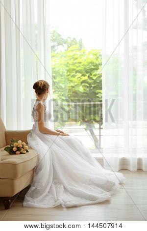 Bride in beautiful dress with wedding bouquet sitting on sofa