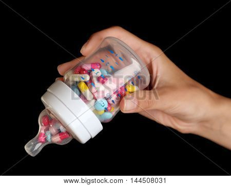 Female hand holding feeding bottle full of pills on black background