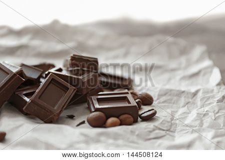 Pile of dark chocolate bars with roasted coffee beans on paper background