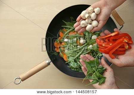 Male and female hands holding vegetables above pan on wooden table, top view