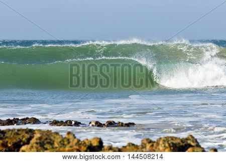 Large wave breaking with rocks in the foreground and blue sky
