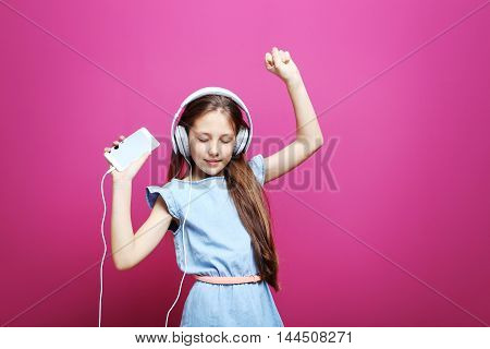 Portrait Of Young Girl With Headphones And Smartphone On Pink Background