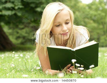 Junge schöne Mädchen, die Lektüre eines Buches im freien