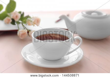 Cup of tea with flowers and notebook on table