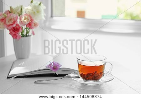 Cup of tea with notebook and spoon on table