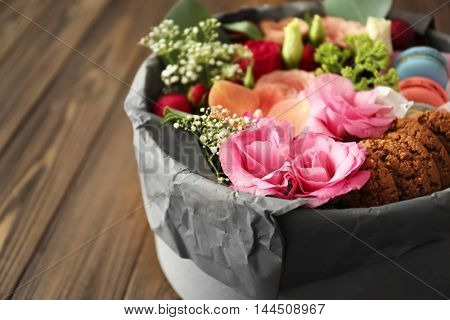 Gift box with flowers and cookies on wooden table closeup