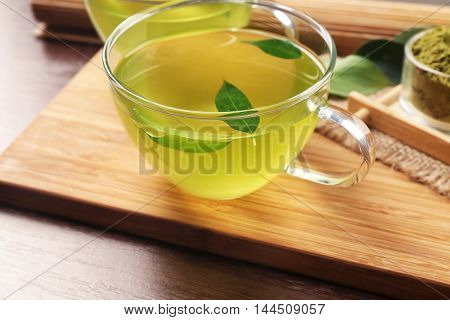 Glass cups of green matcha tea on wooden cutting board closeup