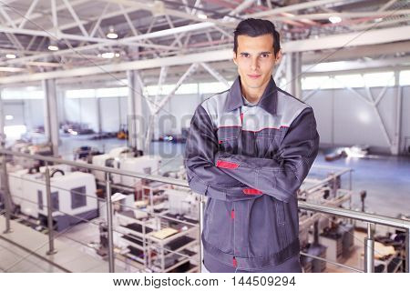Young worker in uniform standing in CNC factory