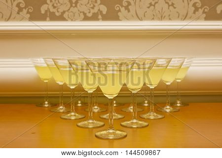 Rows of yellow cocktails in a triangle shape ready to be served