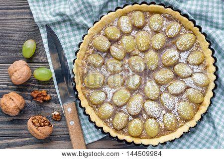 Homemade shortbread dough grape tart with walnut praline top view horizontal