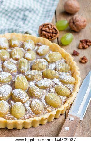 Homemade shortbread dough grape tart with walnut praline vertical closeup