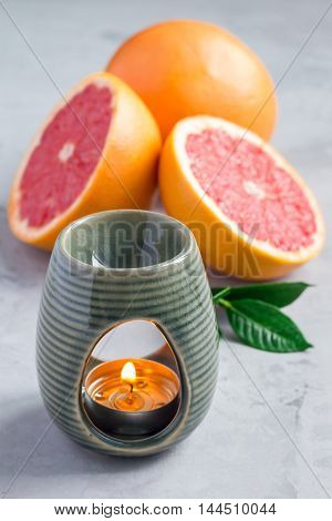 Aroma lamp with grapefruit essential oil grapefruits on background vertical