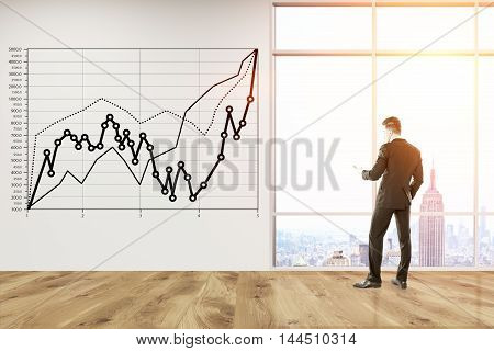 Man in suit looking at New York through big office window. Graph sketched on concrete wall. Concept of business strategy development. Toned image