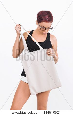 Girl in white shorts holding big canvas bag and looking down. She is dressed in black tank top and wearing glasses with black frame. Concept of product placement. Mock up. white background.