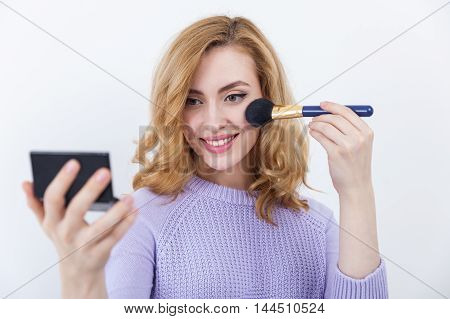 Smiling girl in beautiful sweater holding brush and powder and applying makeup to her face. Concept of beauty