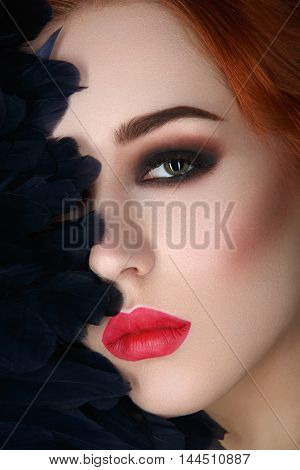 Beautiful young woman with smoky eyes and full red lips. Half of face covered with blue feathers. Studio closeup beauty shot. Copy space.