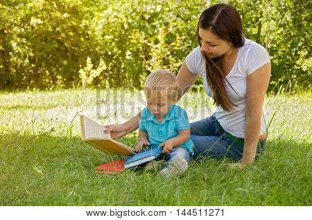mother reads to her child an interesting book in the park
