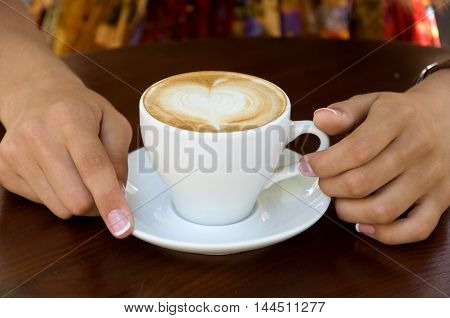 woman holding a cup of delicious hot coffee