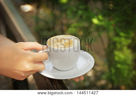 Female hands holding cup of coffee on blurred natural background