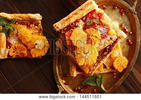 Tray with citrus cake slices on wooden background